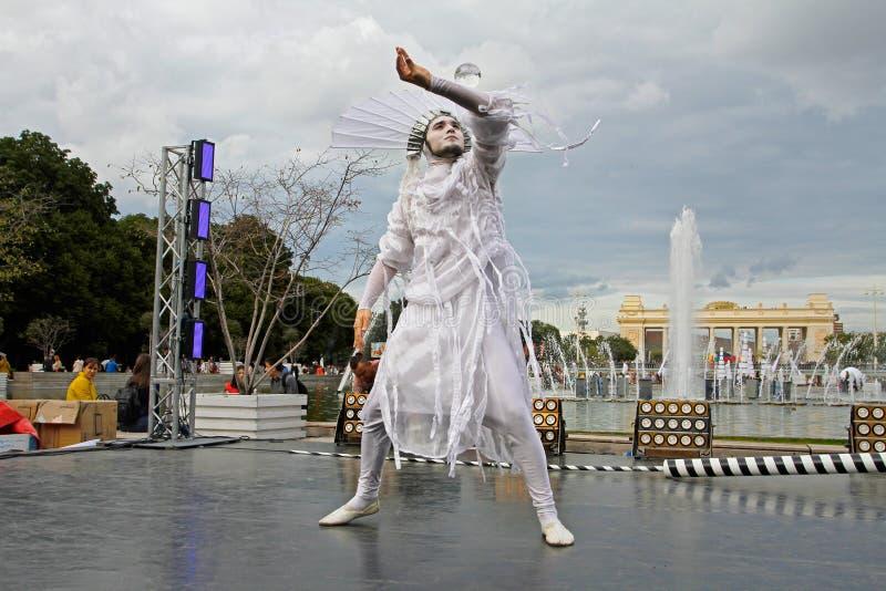 Artista de sexo masculino de la calle con una bola de cristal en el ` brillante de la gente del ` del festival en el parque Gorko foto de archivo libre de regalías