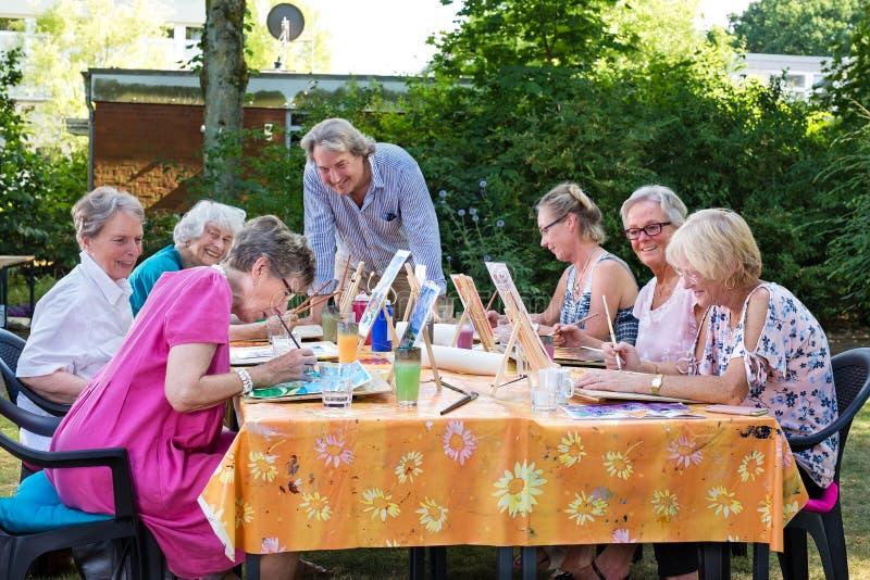 Artista de sexo masculino que da lecciones del arte al grupo de mujeres mayores, practicando en las imágenes de pintura que asist fotos de archivo