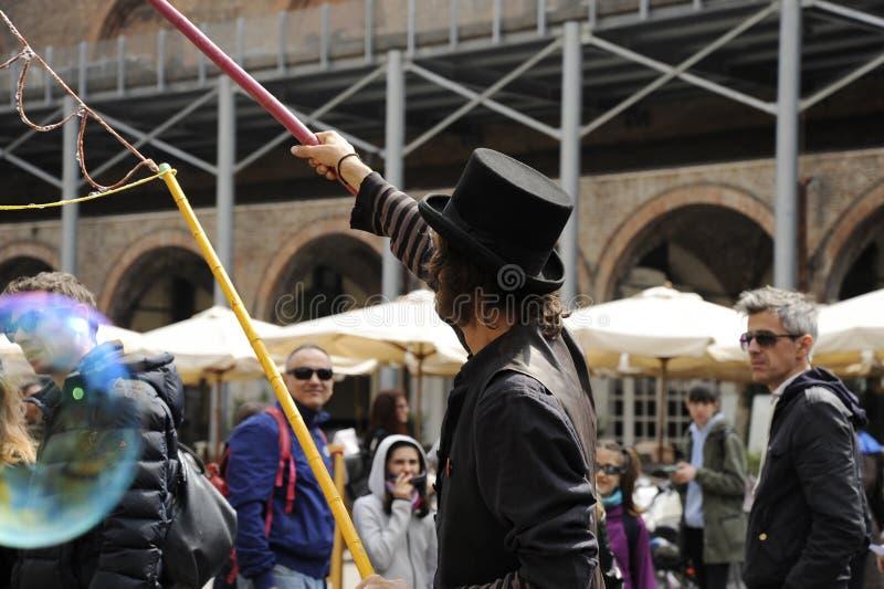 Artista del hombre con el sombrero negro que hace burbujas de jabón Demostración de la burbuja de jabón en la calle stock de ilustración