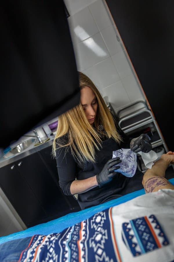 Artista del tatuaje con el dibujo ella va a tatuar en su cli fotos de archivo libres de regalías