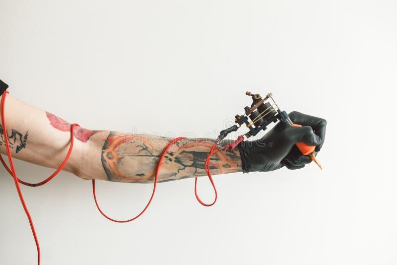 Artista del tatuaje de la mano con la máquina del tatuaje fotos de archivo libres de regalías