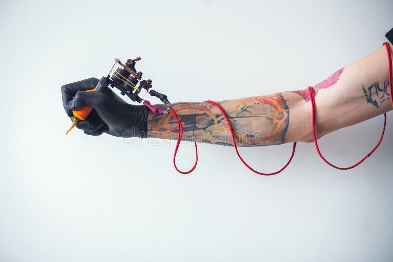 Artista del tatuaje de la mano con la máquina del tatuaje imágenes de archivo libres de regalías