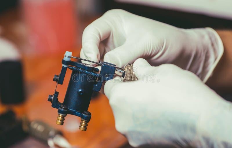 artista del tatuaje en los guantes blancos de goma que consiguen listos para hacer un tatuaje en el salón fotografía de archivo