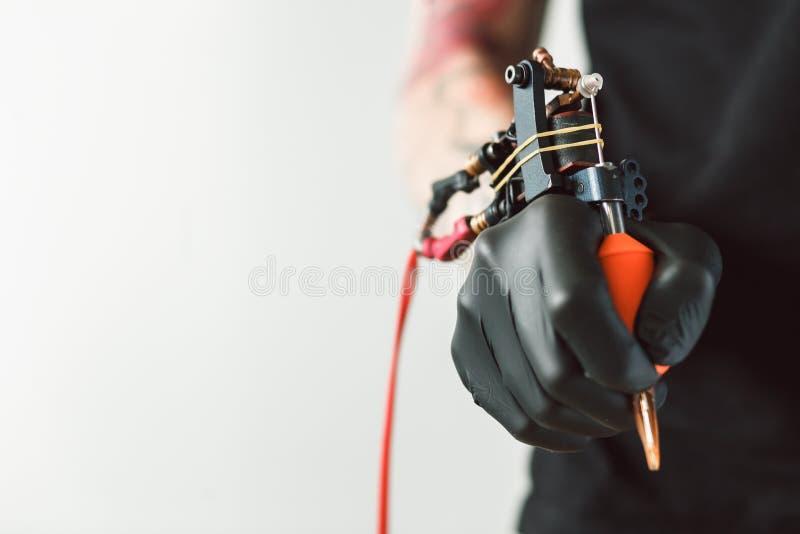 Artista del tatuaje que sostiene la máquina del tatuaje foto de archivo