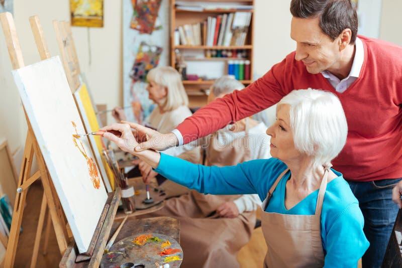 Artista deleitado que ajuda a mulher idosa no estúdio da pintura imagem de stock