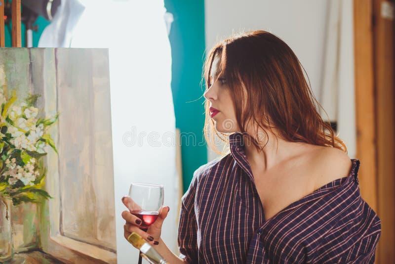 Artista della donna che dipinge un'immagine in uno studio PA pensieroso creativo fotografie stock