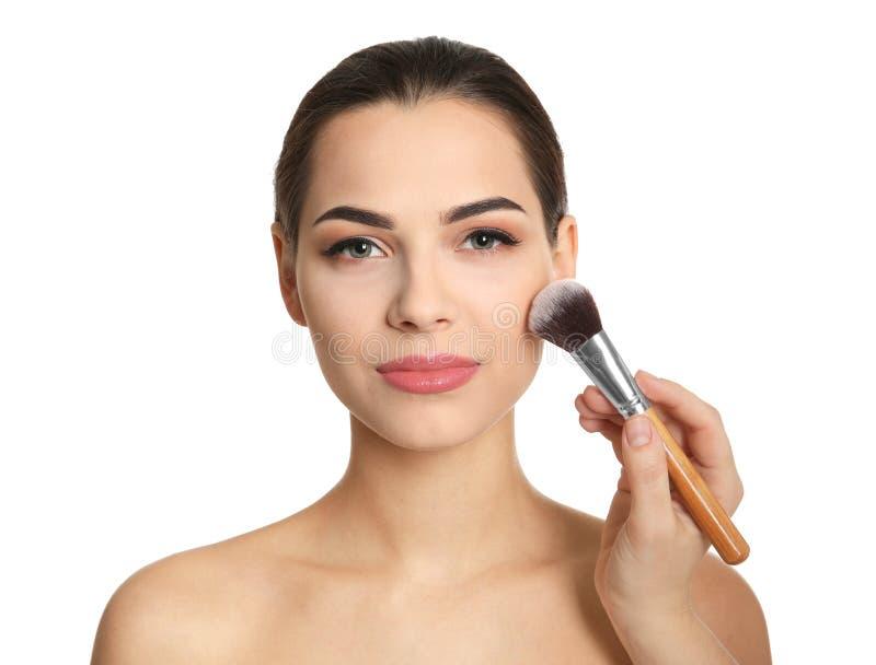 Artista di volto che applica trucco sul fronte del ` s della donna contro il fondo bianco Prodotti cosmetici professionali immagini stock