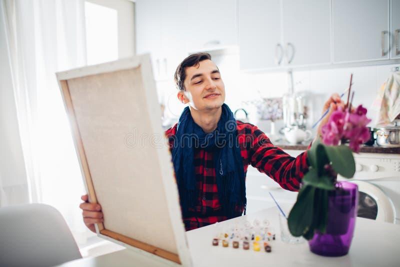 Artista do homem novo que pinta em casa a pintura criativa imagem de stock royalty free