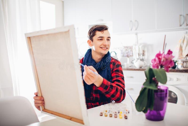 Artista do homem novo que pinta em casa a pintura criativa fotos de stock
