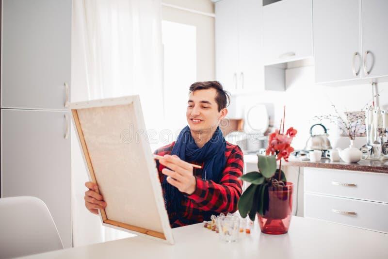 Artista do homem novo que pinta em casa a pintura criativa ilustração stock