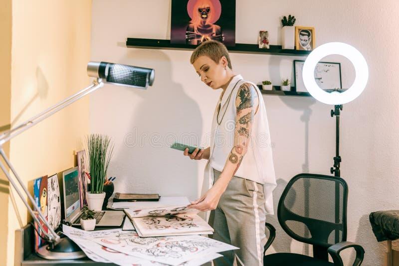 Artista elegante concentrado da tatuagem que verifica seus álbuns com os esboços imagem de stock