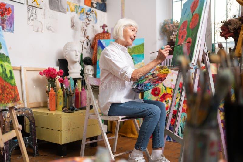Artista envelhecido que sente satisfeito verdadeiramente ao pintar papoilas vermelhas imagens de stock
