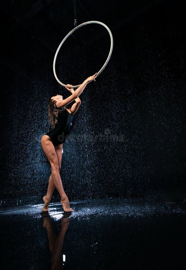 Artista fêmea bonito novo do circo com aro aérea imagens de stock royalty free