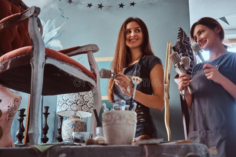 Artista fêmea com seu assistente nos aventais que pintam a cadeira do vintage com o pincel na oficina foto de stock
