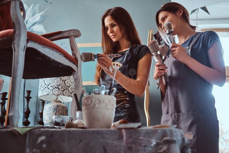 Artista fêmea com seu assistente nos aventais que pintam a cadeira do vintage com o pincel na oficina fotos de stock royalty free