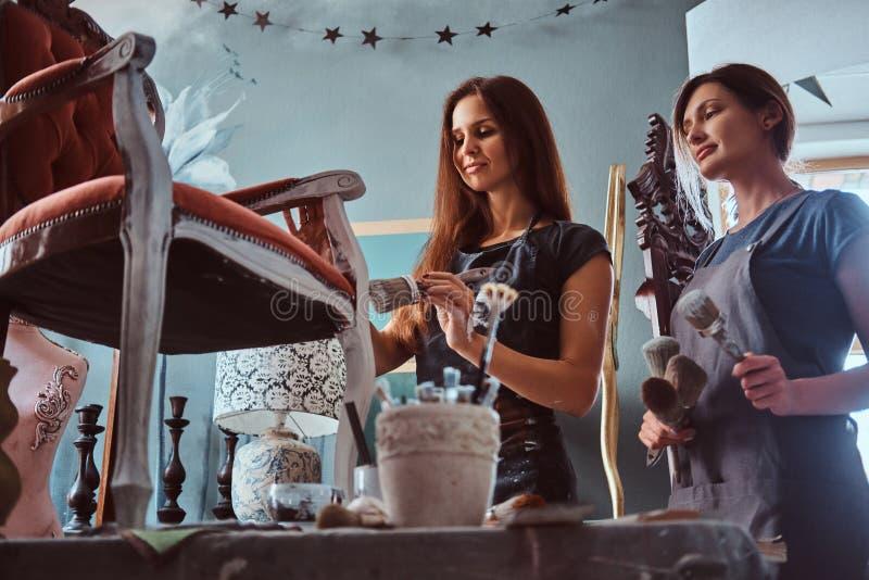 Artista fêmea com seu assistente nos aventais que pintam a cadeira do vintage com o pincel na oficina fotografia de stock