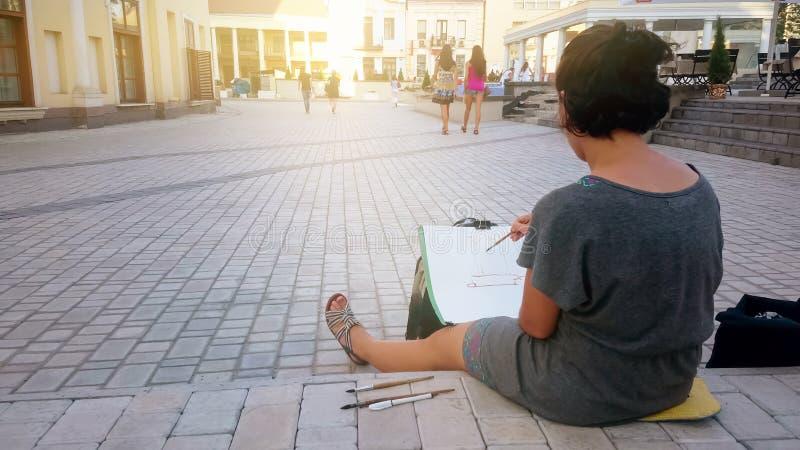 Artista fêmea inspirado da rua que senta-se no pavimento e a pintura, a arte e o passatempo foto de stock royalty free