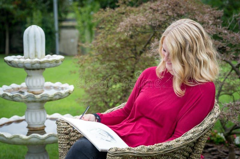 Artista fêmea louro no jardim fotografia de stock royalty free