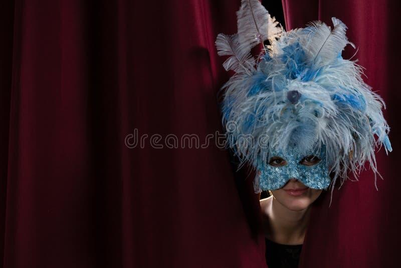 Artista fêmea na máscara do disfarce que espreita através da cortina vermelha imagem de stock royalty free