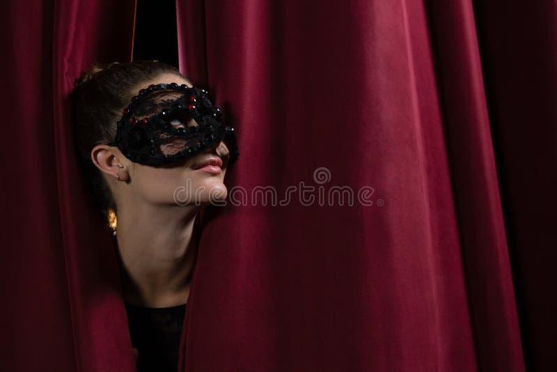 Artista fêmea na máscara que espreita através da cortina vermelha imagens de stock royalty free