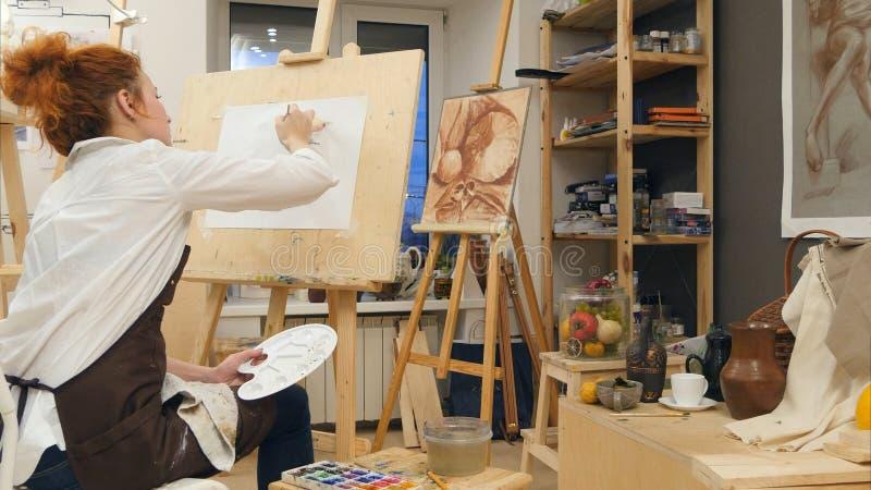 Artista fêmea novo que usa a pintura da paleta em sua oficina fotos de stock royalty free