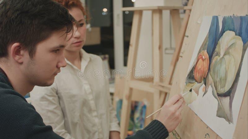 Artista fêmea que ensina o estudante masculino novo pintar com aquarela fotos de stock