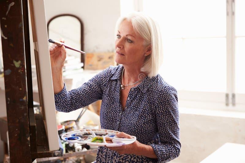 Artista fêmea Working On Painting no estúdio imagens de stock