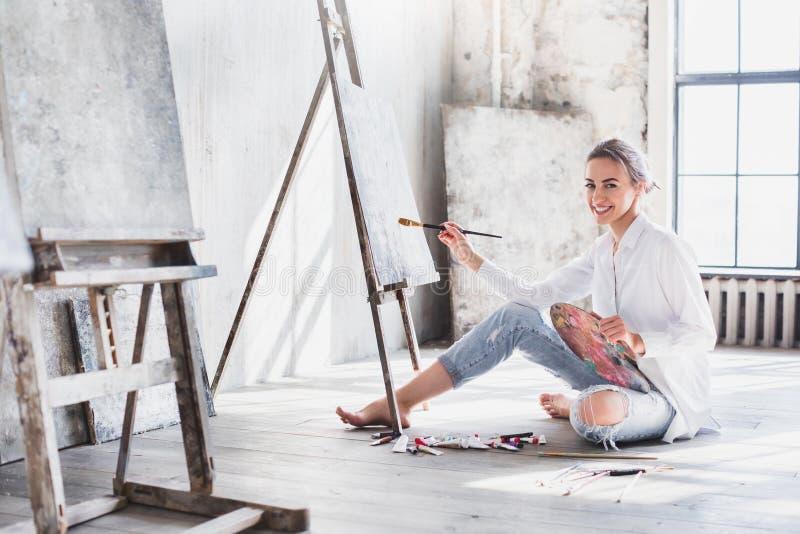 Artista fêmea Working On Painting no estúdio brilhante da luz do dia foto de stock royalty free