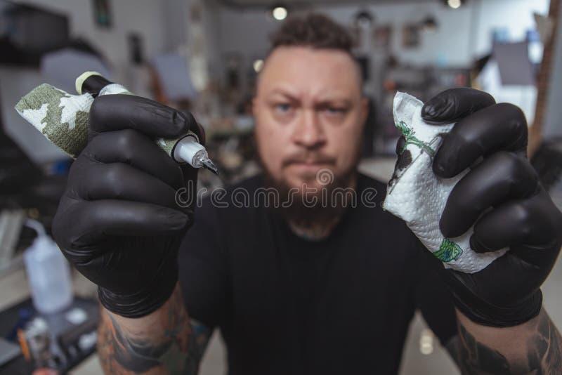 Artista farpado expressivo da tatuagem que trabalha em sua loja da tatuagem imagens de stock