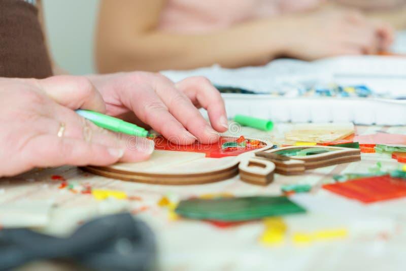 Artista femminile delle mani raccogliere mosaico vicino su fotografia stock