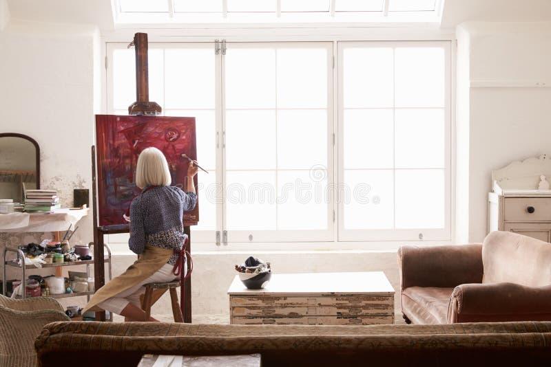 Artista femminile Working On Painting nello studio luminoso di luce del giorno immagine stock libera da diritti