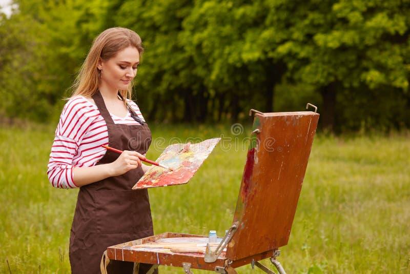 Artista inspirado talentoso que guarda o equipamento profissional em ambas as mãos, pintando no ar livre, afeiçoado da natureza,  fotografia de stock royalty free