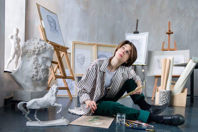 Artista joven del estudiante en el lugar de trabajo del arte foto de archivo