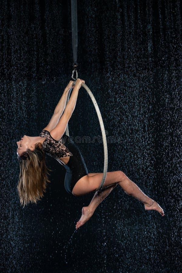 Artista magro bonito novo do circo na aro aérea que levanta em um fundo preto do estúdio do aqua fotos de stock royalty free
