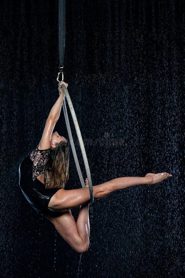 Artista magro bonito novo do circo na aro aérea que levanta em um fundo preto do estúdio do aqua fotografia de stock