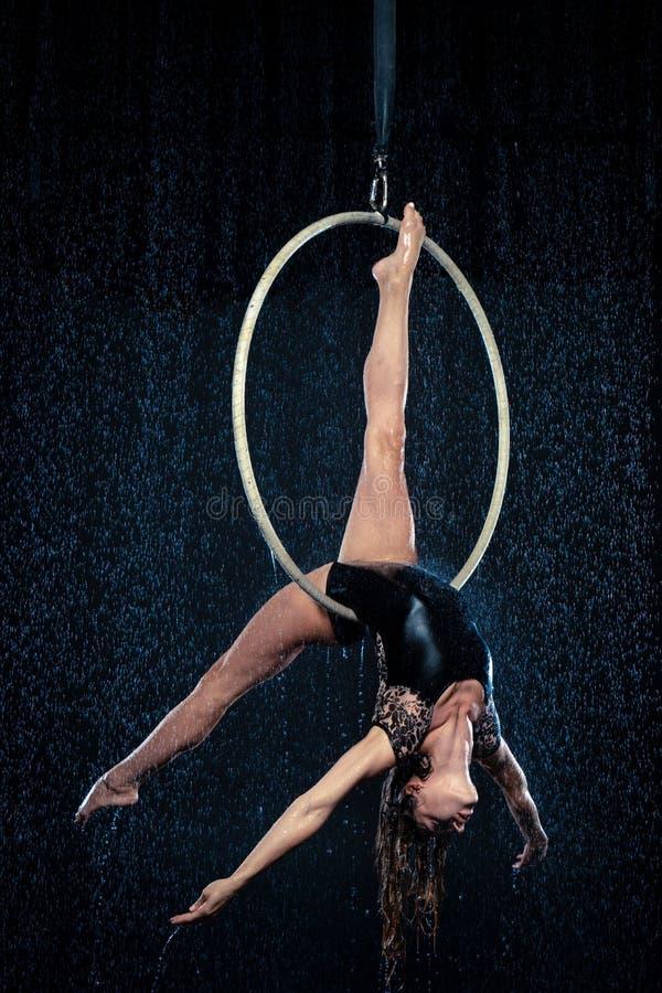Artista magro bonito novo do circo na aro aérea que levanta em um fundo preto do estúdio do aqua foto de stock