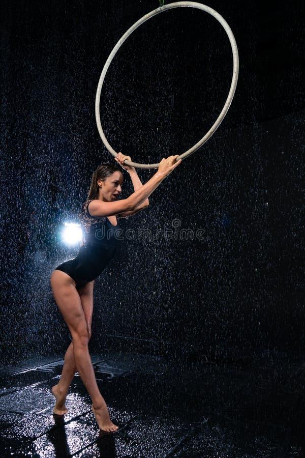 Artista magro bonito novo do circo que guarda uma aro aérea que levanta em um fundo preto do estúdio do aqua fotos de stock