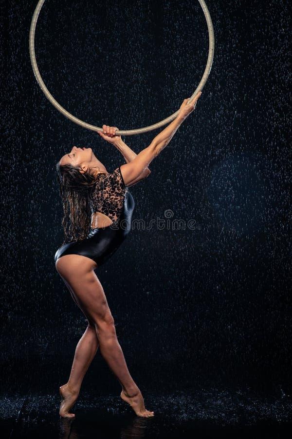 Artista magro bonito novo do circo que guarda uma aro aérea que levanta em um fundo preto do estúdio do aqua fotografia de stock