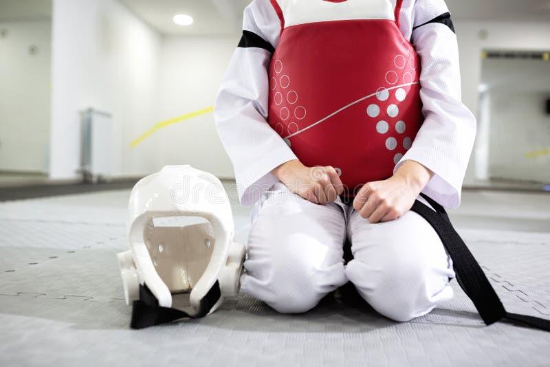 Artista marziale in ingranaggio protettivo che si siede e che tiene un casco, cintura nera, uniforme bianca fotografia stock