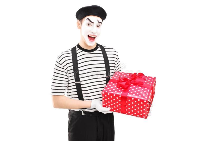 Artista maschio del mimo che tiene un contenitore di regalo e che esamina macchina fotografica fotografia stock libera da diritti