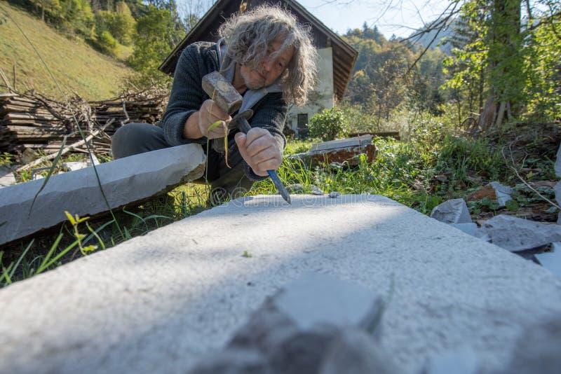 Artista mayor que trabaja tallando la piedra fotografía de archivo