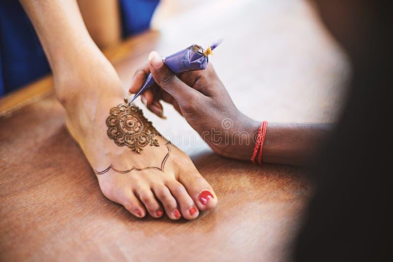 Artista Mehndi del hennè che dipinge il piede delle donne sul giorno delle nozze indiano immagini stock
