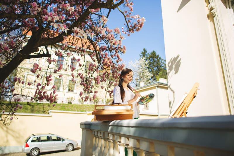 Artista moreno joven de la mujer que sostiene en manos un cepillo y una paleta Cerca de ella el ?rbol de la magnolia y el diverso fotos de archivo