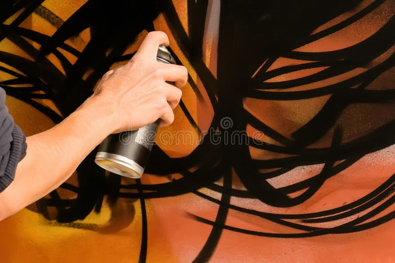 Artista Paint Spraying de la pintada del varón adulto la pared, foto de archivo