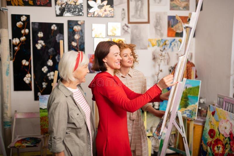 Artista pensionato vicino ai giovani studenti che attingono tela fotografie stock libere da diritti