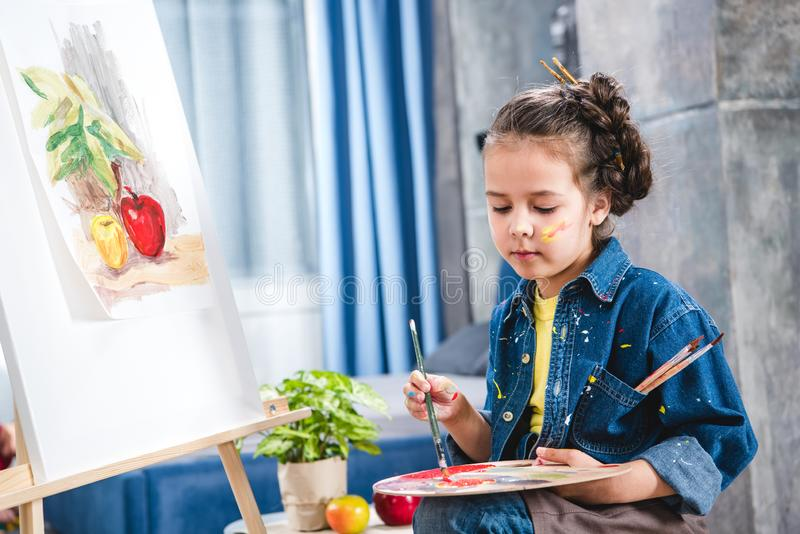 Artista pequeno que guarda a paleta e que pinta a imagem fotografia de stock