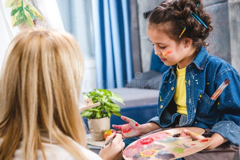 Artista pequeno que guarda a paleta e que pinta a imagem imagens de stock royalty free