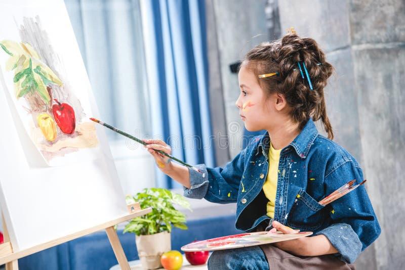 Artista pequeno que guarda a paleta e que pinta a imagem foto de stock royalty free