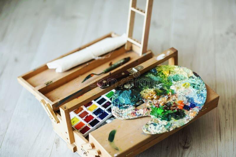 Artista plegable de madera de la maleta con los cepillos, la pintura y la paleta Fondo de un piso de madera imágenes de archivo libres de regalías