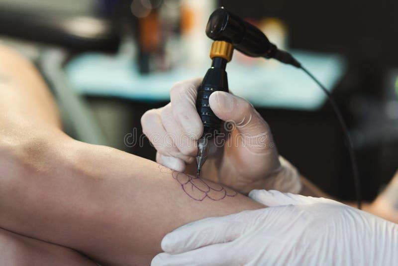 Artista profesional del tatuaje que hace el tatuaje a mano imagen de archivo libre de regalías
